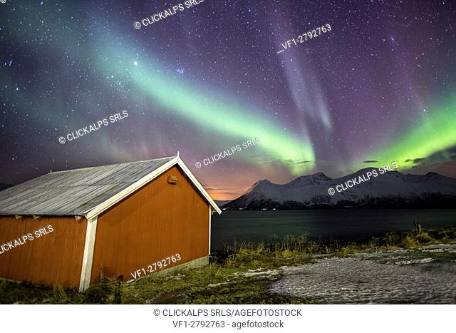 Northern Lights illuminates the wooden cabin at Svensby Lyngen Alps Tromsø Lapland Norway Europe