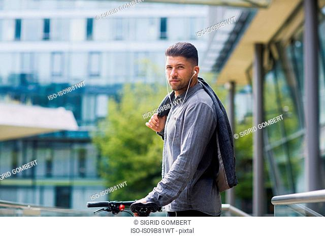 Man with headphones carrying jacket over shoulder looking at camera