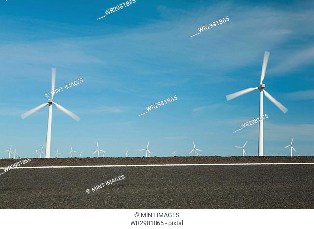 Wind turbines, tall white towers in the flat plains by a road near the Columbia River Gorge