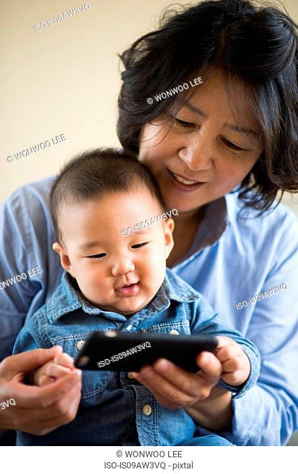 Grandmother showing smartphone to grandson
