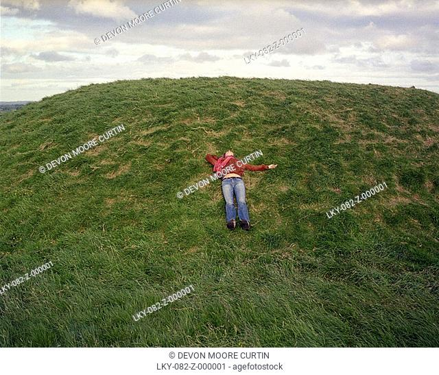 Woman lying on grass on hill in Ireland
