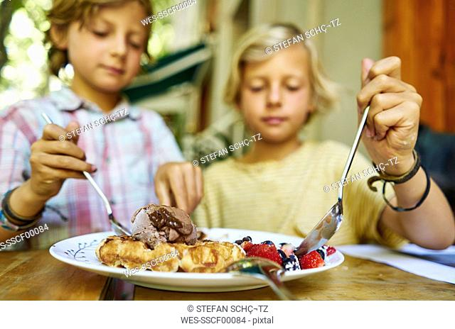 Two boys sitting at table eating ice cream