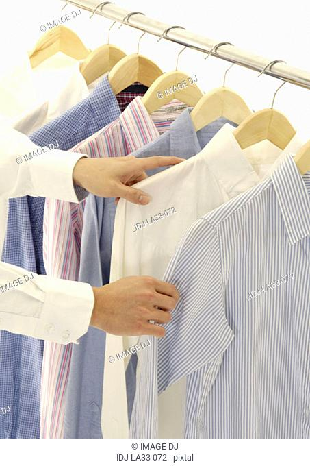 Cropped view of a woman selecting a shirt