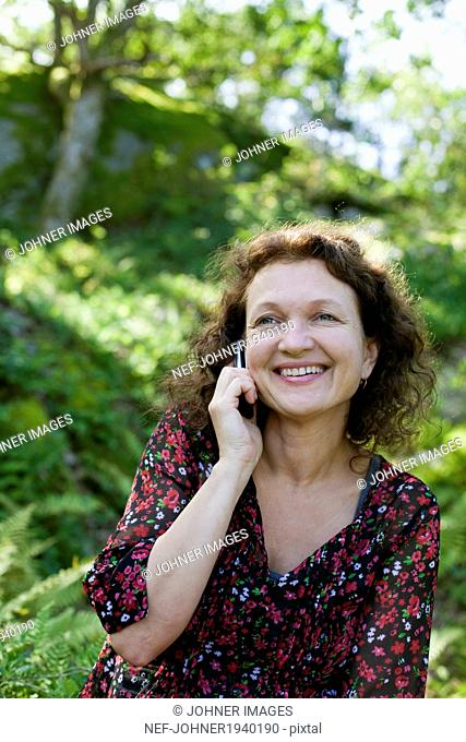 Smiling mature woman talking via cell phone