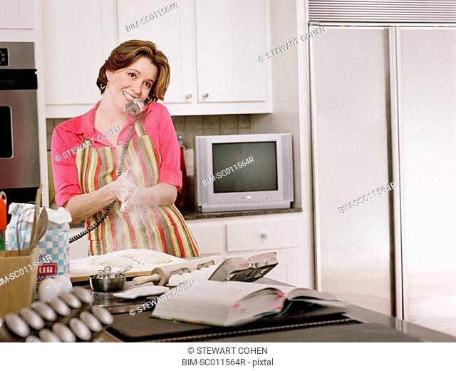 Young woman baking as she talks on the phone