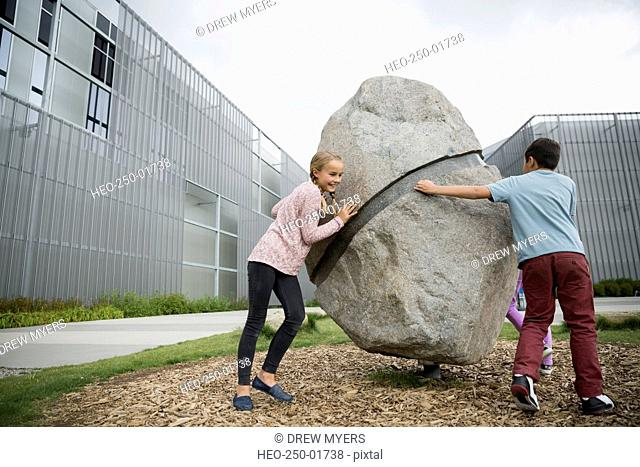 Boy and girl circling large boulder at playground