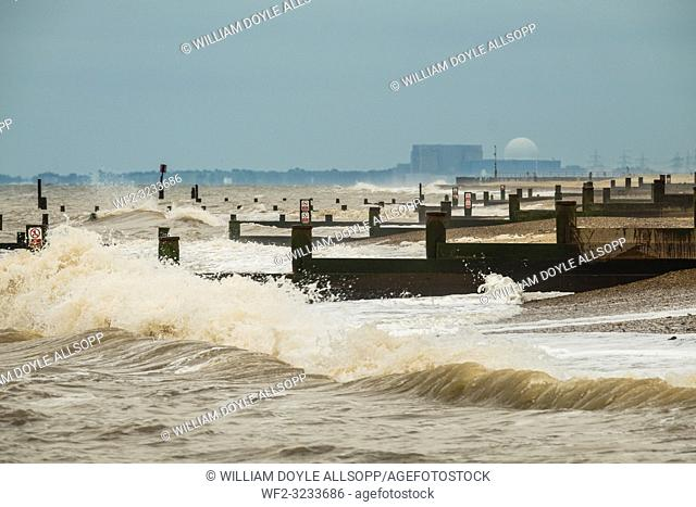 Waves break on the beach and groynes at Southwold with Sizewell nuclear power station in the distance