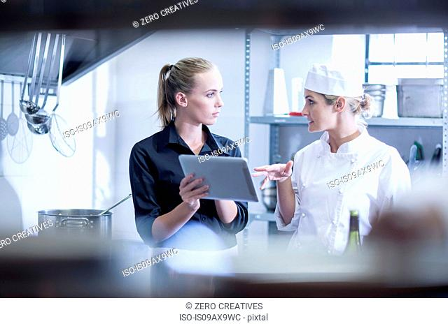 Waitress and chef discussing orders on digital tablet in kitchen