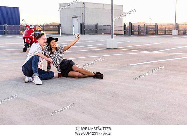 Happy young couple with motor scooter on parking level taking a selfie