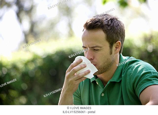 A young man outdoors, sneezing