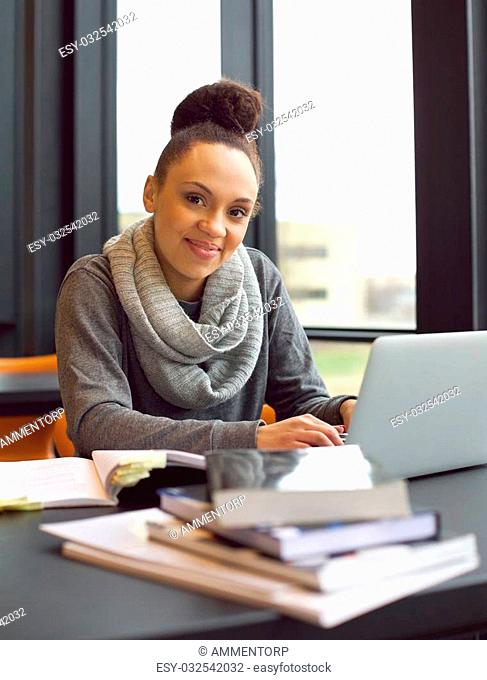 Happy young african american woman student with laptop and books sitting at table looking at camera smiling. Female student studying in library