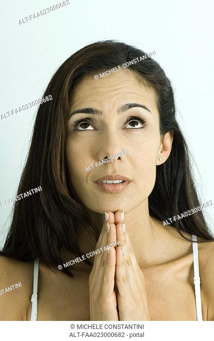 Woman holding hands in prayer, looking up, portrait