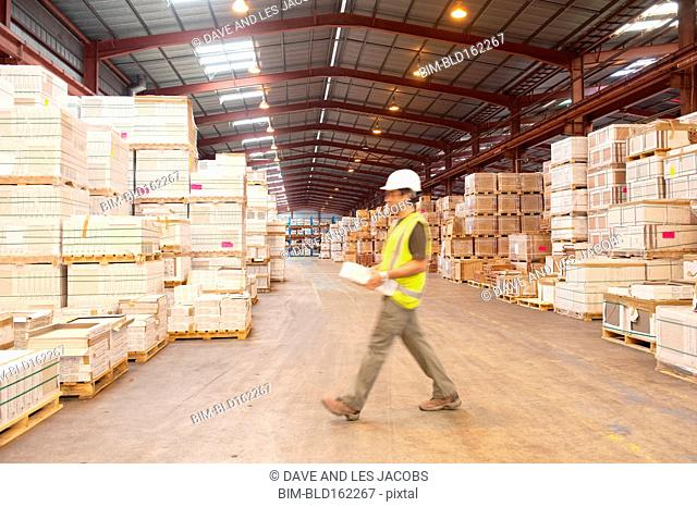 Blurred view of Hispanic worker walking in warehouse