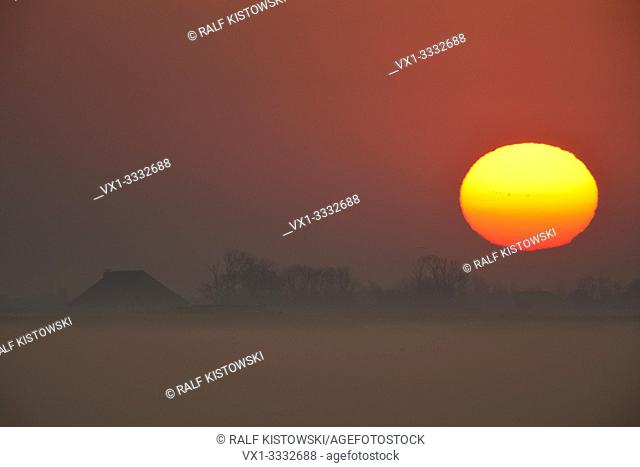 Breathtaking sunrise above a farmhouse and some fields covered with early morning mist, red colored sky, sun loooks like a huge fireball, Europe