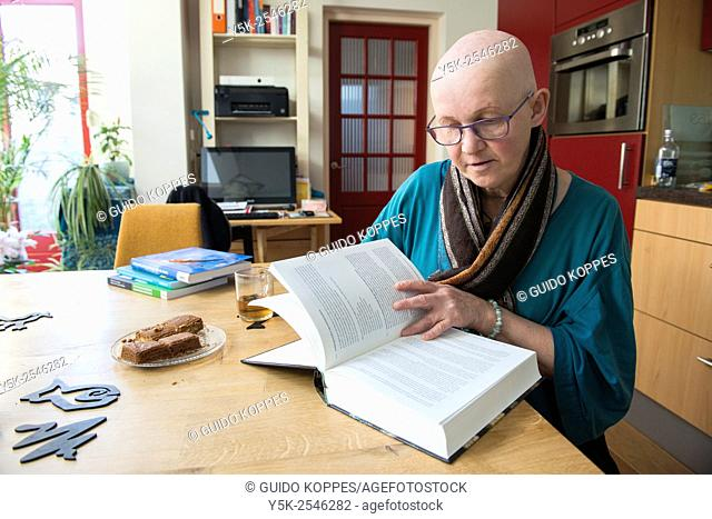 Tilburg, Netherlands. Portrait of a 55 year old, bald female, wearing glasses, born with a genetic disorder, cousing AEC Syndrome / AE Syndrome