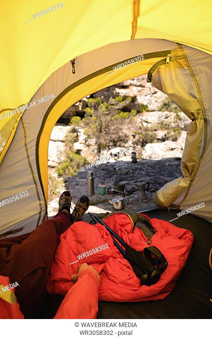 Hiker lying in a tent with camping equipment