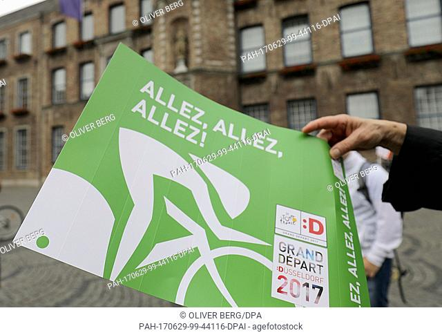A woman holds in her hands a a foldable cardboard for cheering on cyclists in front of city hall in Dusseldorf, Germany, 28 June 2017