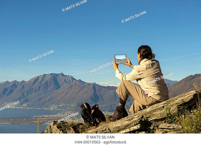 Woman Taking Photos With Her Digital Tablet From a Mountain Top in Ticino, Switzerland