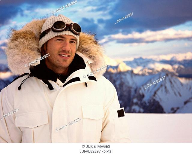 Close up of man in winter clothing with snowy mountains in background