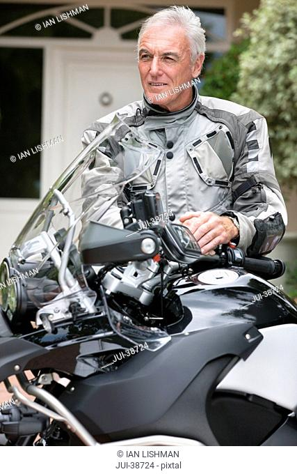 Serious senior man standing next to motorcycle in driveway
