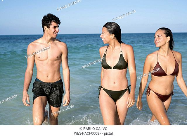 Happy friends walking in the sea