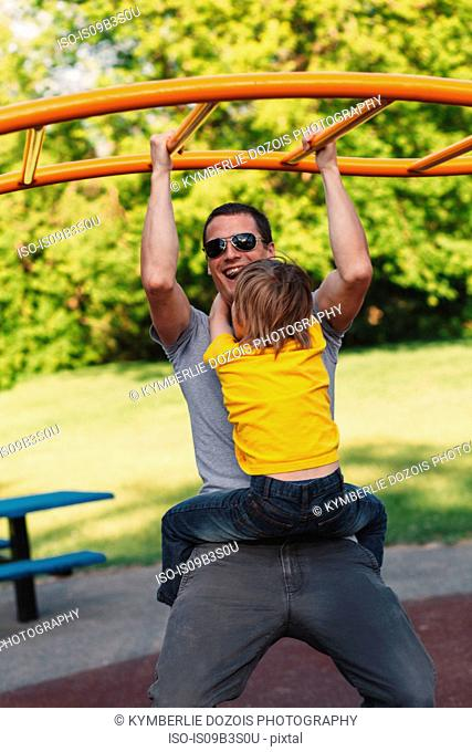 Young man hanging with son from park climbing frame