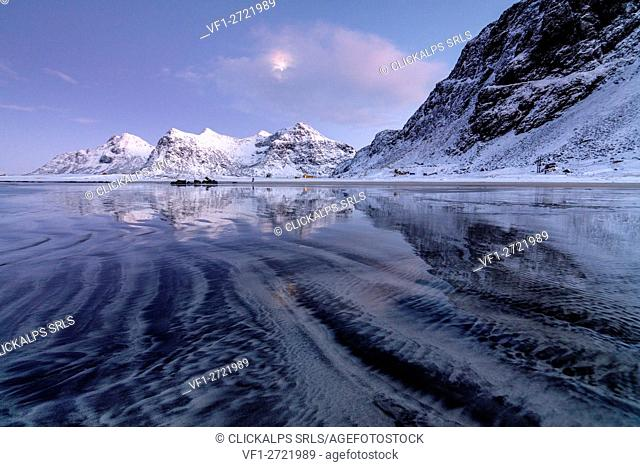 Waves and ice on the surreal Skagsanden beach surrounded by snowy peaks Flakstad Nordland county Lofoten Islands Norway Europe