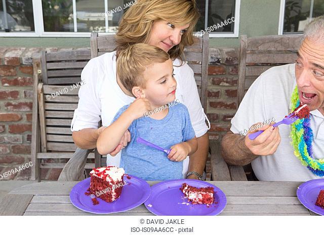 Grandson and mother watching senior man eat birthday cake