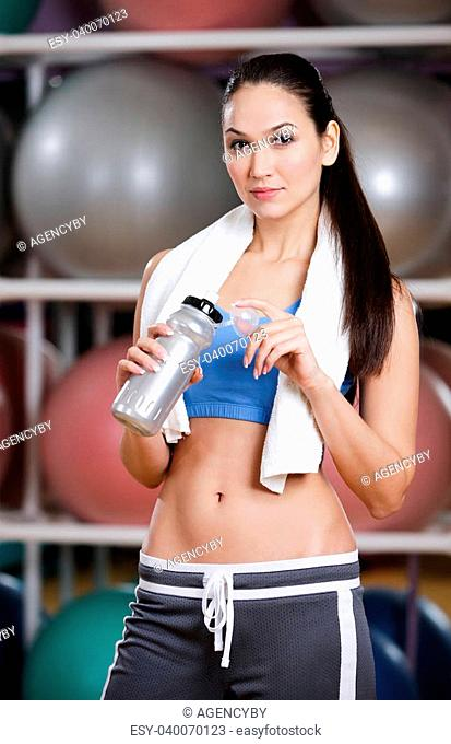 Portrait of sporting young woman in sportswear holding a water bottle in gym after gymnastics. Healthy lifestyle