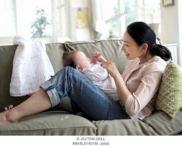 Asian mother playing with baby in living room