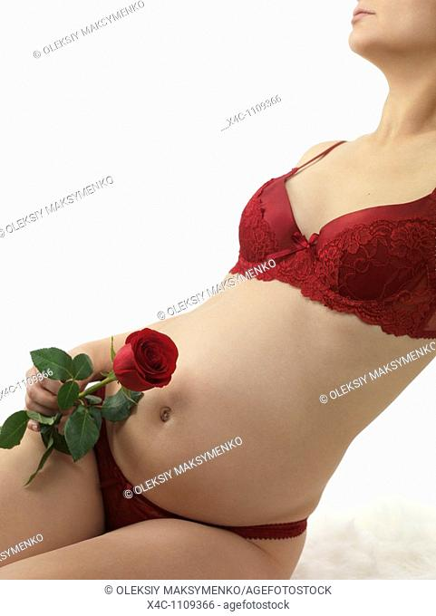 Pregnant woman with a red rose in her hand sitting on a bed