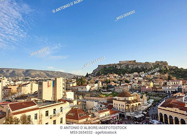 Aerial view of Athens at sunset with the Acropolis in the background. In foreground tourists and local people in Monastiraki Square