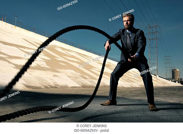 Businessman using gym ropes, Los Angeles river, California, USA