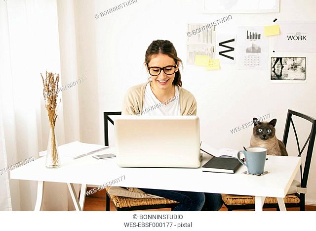 Woman and her cat sitting at desk