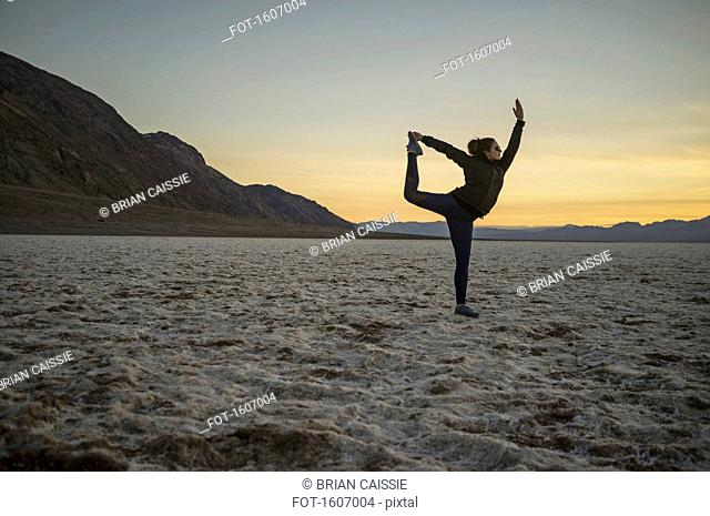 Full length of young woman doing yoga in desert at sunset, Death Valley, Nevada, USA
