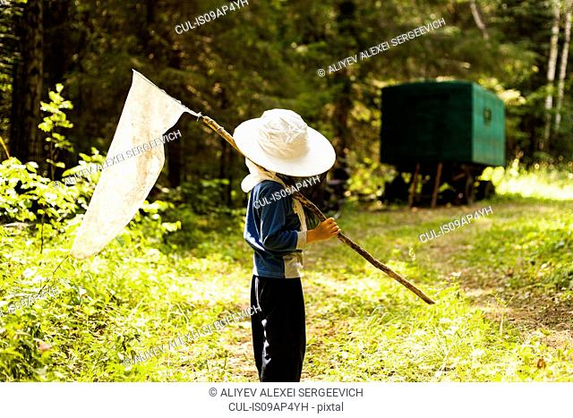 Boy in woods with butterfly net, Sarsy village, Sverdlovsk Region, Russia