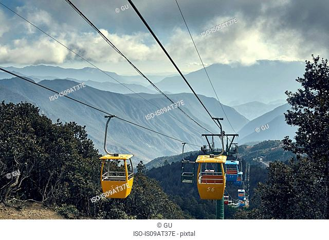 Mountain range and yellow cable cars at Yak Meadow, Lijiang, Yunnan, China