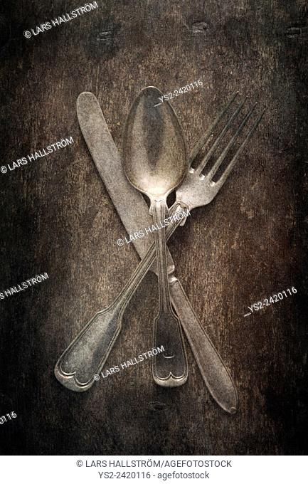 Still life with silverware on table. Knife, fork and spoon on a wooden table