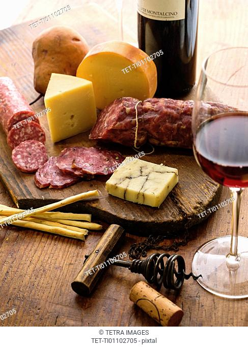 Assorted cheeses with salami and red wine