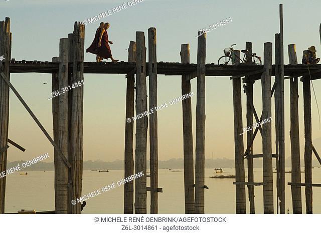 Monk walking at Sunrise over the lake near wooden foot bridge U Bein Bridge crossing the Taungthaman Lake near Amarapura in Mandalay Myanmar