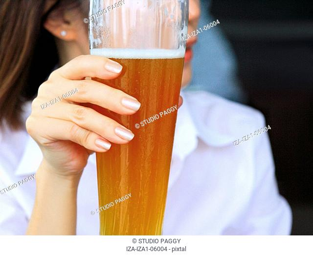 Close-up of a woman holding a glass of beer