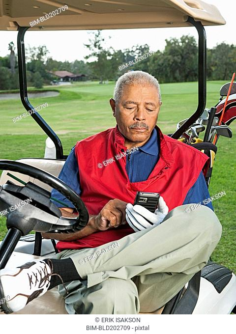 Black man using cell phone in golf cart