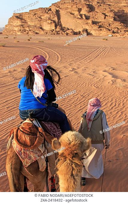 Wadi Rum, Jordan: Tourist riding a camel at sunset in the Wadi Rum desert, Jordan