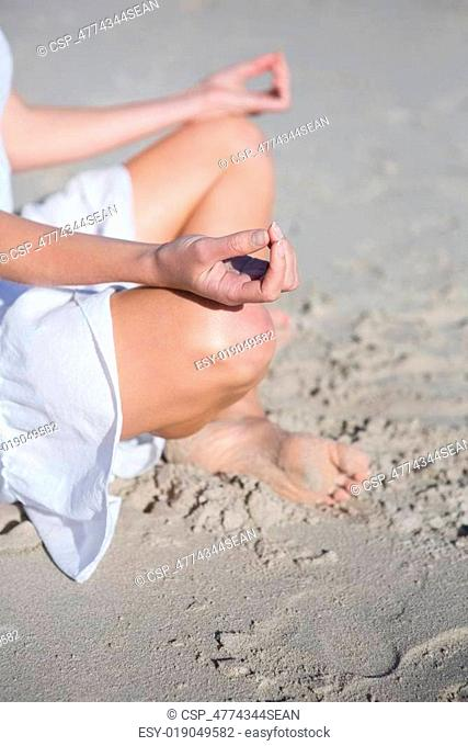 Woman in white dress meditating on the beach