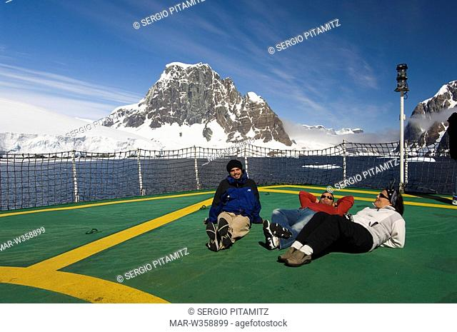 Antarctica, Antarctic Peninsula, Lemaire Channel, Antarctic Dream ship, Tourist relaxing on ship's heliport. MR