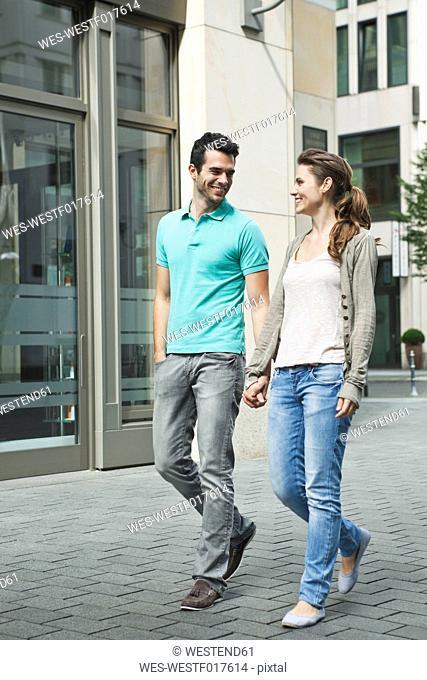 Germany, Berlin, Couple walking hand in hand through city street