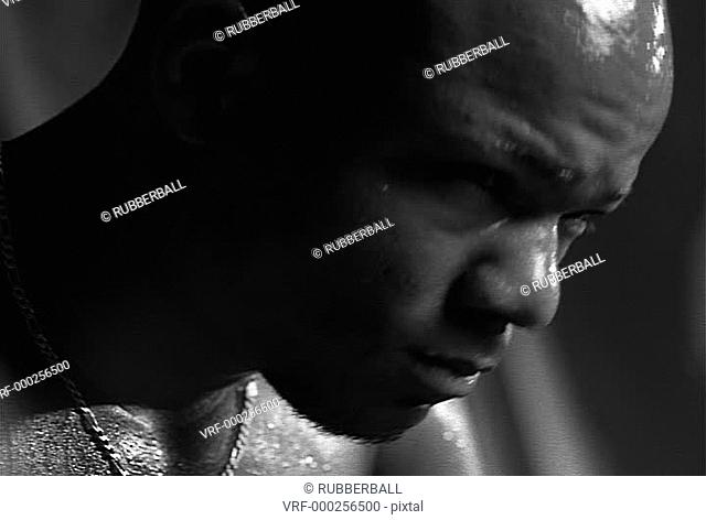 black and white close up portrait of an african american male as he sweats and looks up sternly