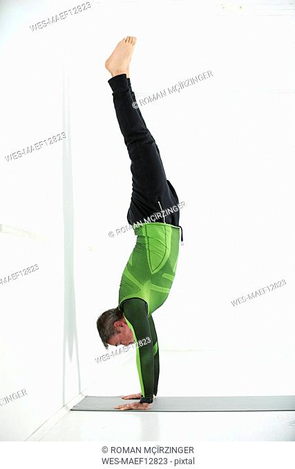 Man doing his fitness regime, practising handstand