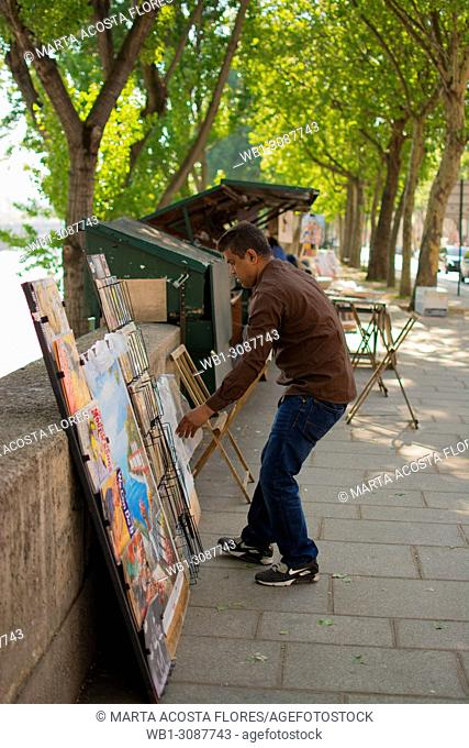 Traditional books and gifts seller (bouquiniste) organizing the display of his products next to the banks of the Seine. Paris, France