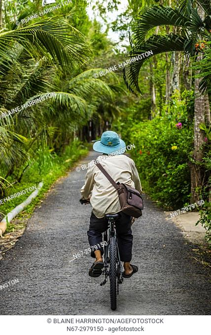 A man bicycling near the backwaters in Cai Lay, Mekong Delta, Vietnam